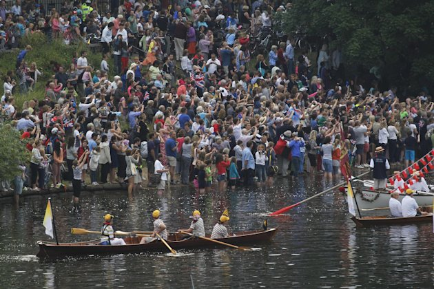 Spectators line the bank of river Thames to watch the royal barge Gloriana, (not shown) carrying the Olympic flame after it left Hampton Court Palace in London, on its way into central London on the final day of the Torch Relay, Friday, July 27, 2012. (AP Photo/Sang Tan)