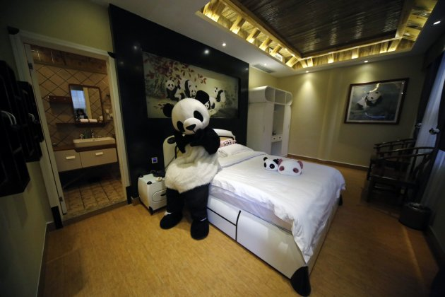 An employee dressed in a panda costume poses for a photo during the soft opening of a panda-themed hotel at the foot of Emei Mountain