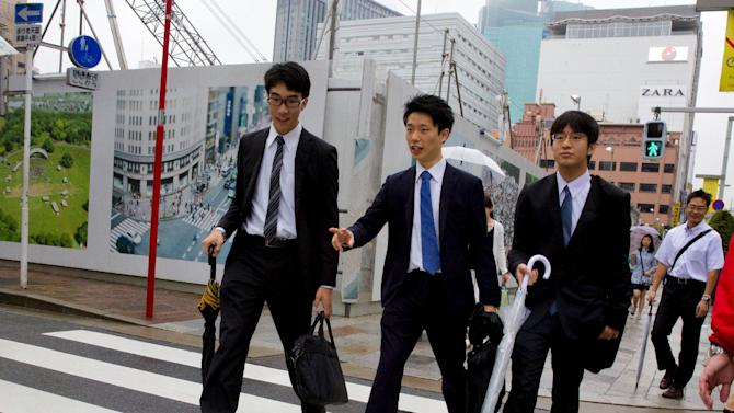Young businessmen cross street during lunch hour in Tokyo