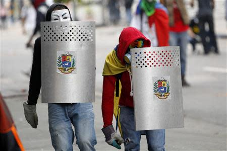Anti-government protesters cover themselves with shields during riots in Caracas