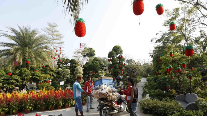 A man sells snacks to workers in a garden centre decorated for Chinese New Year in Kuala Lumpur