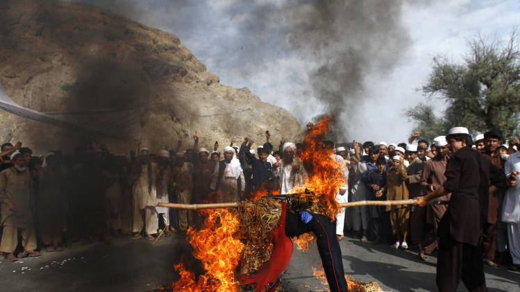 Afghans burn an effigy of the US President Barack Obama in the Ghanikhel district of Nangarhar province, east of Kabul, Afghanistan, Friday, Sept. 14, 2012 during a protest against an anti-Islam film which depicts the Prophet Muhammad as a fraud, a womanizer and a madman. (AP Photo/Rahmat Gul)