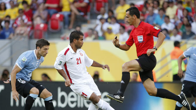 Referee Pedro Proenca of Portugal , right, jumps to avoid being hit by a ball kicked by Tahiti's Samuel Hnanyine, center, during a soccer Confederations Cup group B match against Uruguay at the Arena Pernambuco in Recife, Brazil, Sunday, June 23, 2013. (AP Photo/Eugene Hoshiko)