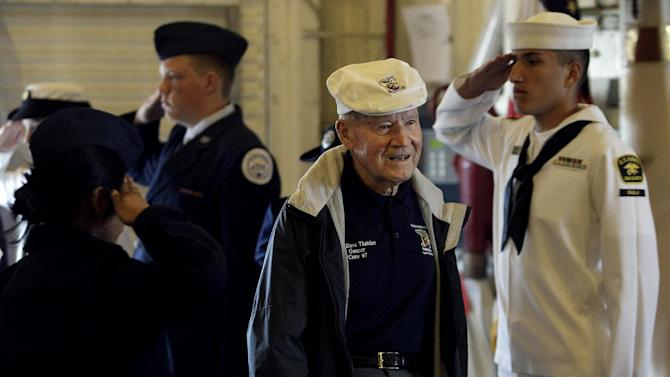 """Staff Sergeant David Thatcher, center, is saluted as he enters the USS Hornet before a news conference to commemorate the 70th Anniversary of the Tokyo attack by the Doolittle Raiders in Alameda, Calif., Saturday, May 5, 2012. Survivors of a daring World War II aerial bombing of Japan are gathering in Alameda on the 70th anniversary of the attack. The """"Doolittle Raiders"""" have been credited with lifting the nation's spirits after Pearl Harbor. (AP Photo/Jeff Chiu)"""