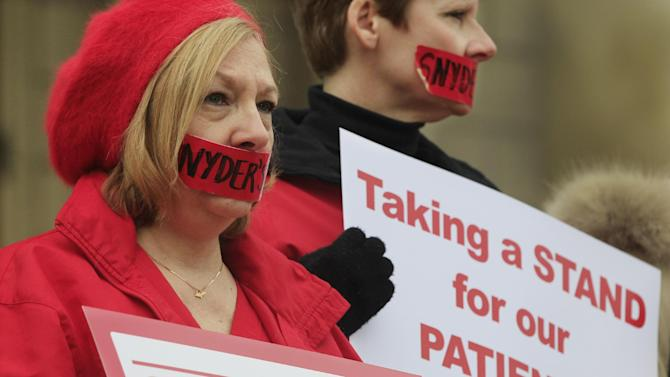 Debbie Nault from the Michigan Nurses Association stands with other members of the association on the state Capitol steps in Lansing, Mich., Monday, Dec. 10, 2012,  protesting right-to-work legislation. Organizers say the gathering was meant to symbolize the silencing of unions that nurses say will happen should the legislation become law.(AP Photo/Carlos Osorio)