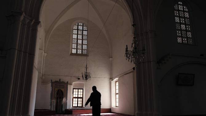 In this photo taken Sunday, March 24, 2013, a man prays inside Selimiye mosque, or Cathedral of St Sophia, in the Turkish Cypriot part of the divided capital Nicosia. Turkish Cypriots have been watching with fascination - and consternation - as the economy of their long prosperous southern brethren implodes. (AP Photo/Petros Giannakouris)