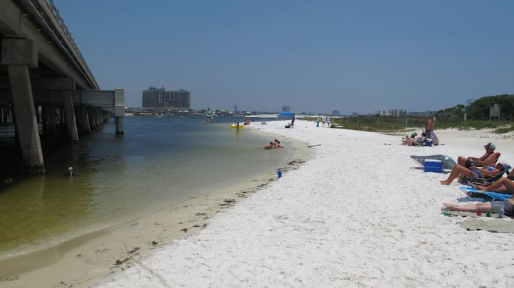 In this July 7, 2014 photo, beachgoers enjoy the shallow beach under a highway bridge in Destin, Fla. The beach is under the controlled of Eglin Air Force Base where it is occasionally used to practice amphibious landings and test high-tech weapons. The public is welcome to use the beach. (AP Photo/Melissa Nelson-Gabriel)