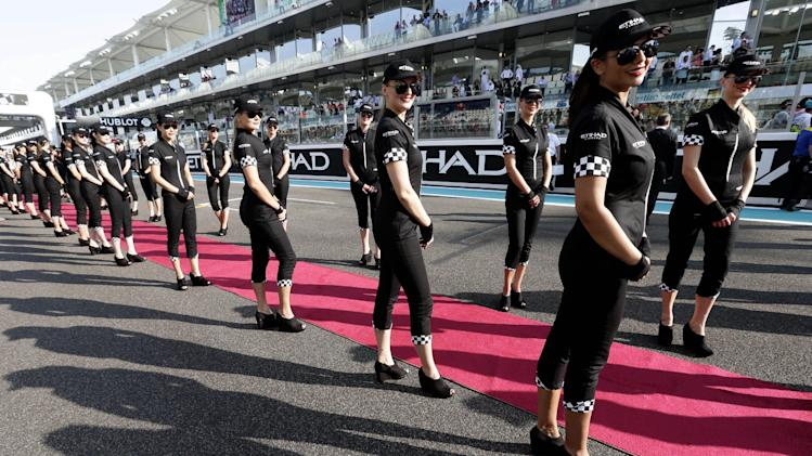 Hostesses wait in the pit lane before the Emirates Formula One Grand Prix at the Yas Marina racetrack, in Abu Dhabi, United Arab Emirates, Sunday, Nov. 4, 2012. The Emirates Formula One Grand Prix will take place on Sunday. (AP Photo/Hassan Ammar)