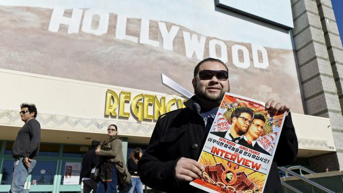 "Rubin Carias holds a poster of the film ""The Interview"" starring actors Seth Rogen and James Franco as he attends the Christmas Day screening of ""The Interview"" in the Van Nuys section of Los Angeles"