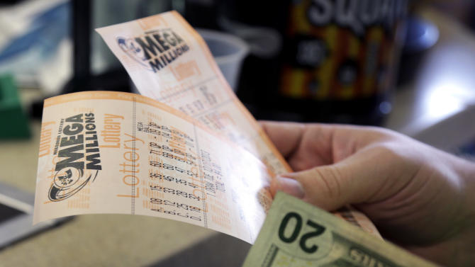 Scott Hoormann holds two Mega Millions lottery tickets he purchased at Energy Express Monday, Dec. 16, 2013, in St. Louis. The Mega Millions jackpot soared to $586 million on Monday amid a frenzy of ticket purchases, a jump that pushed the prize closer to the $656 million U.S. record set last year. (AP Photo/Jeff Roberson)