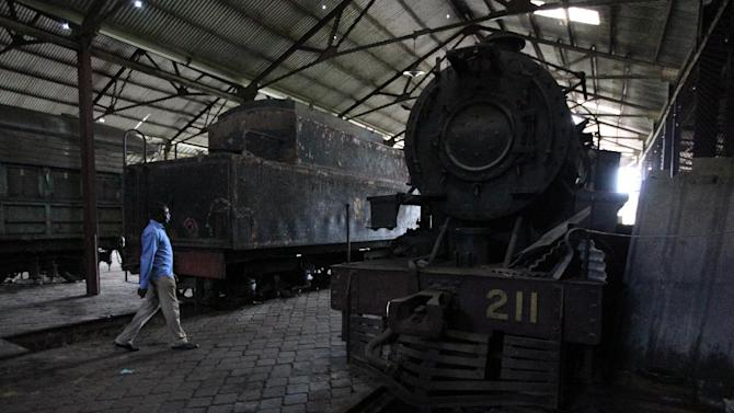 A man walks past an abandoned steam locomotive in Lagos, Nigeria, on Saturday, April 13, 2013. The Nigerian Railway Corp., while recently restarting service from Lagos to the northern city of Kano, still has relics from the past littering the grounds of its headquarters in Lagos. Historians hope to preserve some of these old locomotives and train cars for future generations to see. (AP Photo/Jon Gambrell)