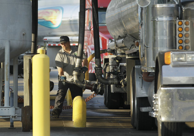 A man moves a fuel hose into position to begin loading gasoline into a tanker truck, Friday, June 29, 2012, at a North Little Rock, Ark., fuel distribution terminal. Oil soared the most in more than three years, on Friday, after European leaders took surprisingly aggressive steps meant to halt a debt crisis that has undermined the regional economy. (AP Photo/Danny Johnston)