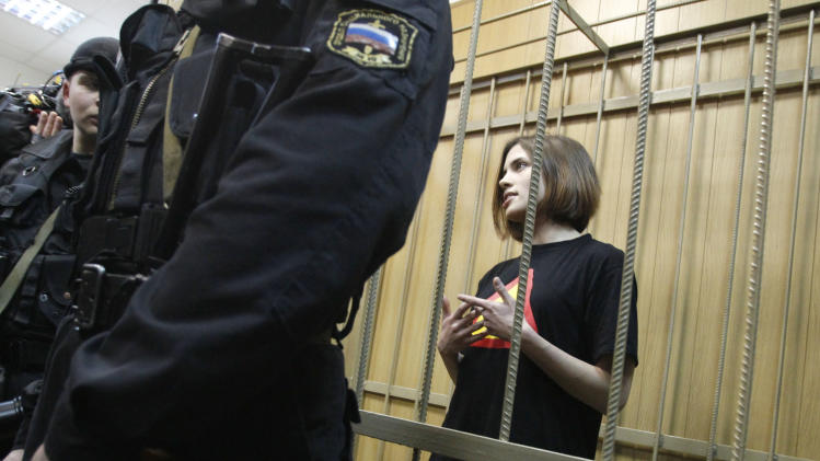 In this Thursday, April 19, 2012 photo, Nadezhda Tolokonnikova, a member of the female punk rocker band Pussy Riot stands in a defendants cage prior to a court hearing in Moscow, Russia. On Saturday, Nov. 1, 2013, the Interfax news agency cited Russia's prison service as saying Tolokonnikova is being sent to a new penal colony. The report comes after complaints by her husband that there had been no contact with Tolokonnikova in recent days.Tolokonnikova is serving two years following the band's politically provocative performance in Moscow's main Orthodox cathedral in 2012. (AP Photo/Ivan Sekretarev)