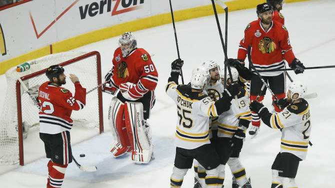 The Boston Bruins celebrate a second period goal against Chicago Blackhawks goalie Corey Crawford (50) as Chicago Blackhawks defenseman Michal Rozsival (32) looks on during Game 2 of the NHL hockey Stanley Cup Finals, Saturday, June 15, 2013, in Chicago. (AP Photo/Charles Rex Arbogast)