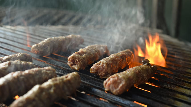 """""""Mici"""", the Romanian version of a Turkish dish, spicy grilled sausages, popular across the Balkans, are grilled in a restaurant in Bucharest, Romania, Sunday, Feb. 16, 2014. Officials in Brussels have agreed that spicy """"mici"""", grilled meat bullet shaped delicacies which rely on a pinch of bicarbonate of soda for their distinctive succulent flavor and puffy texture will be permitted under European Union rules, the Romanian Meat Association says.(AP Photo/Octav Ganea/Mediafax) ROMANIA OUT"""