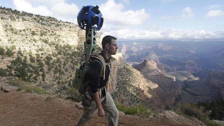 In this Monday Oct. 22, 2012, photo, Google product manager Ryan Falor walks with the Trekker during a demonstration for the media along the Bright Angel Trail at the South Rim of the Grand Canyon National Park in Arizona. The search engine giant is using the nearly 40-pound, backpack-sized camera unit to showcase the Grand Canyon's most popular hiking trails on the South Rim and other off-road sites. It's about 4 feet in height when set on the ground, and when worn, the camera system extends 2 feet above the operator's shoulders.  (AP Photo/Rick Bowmer)