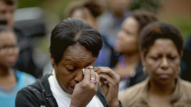 Retired Atlanta police Det. Jaqueline Barber wipes a tear during a news interview while standing with members of Occupy Atlanta and fellow officers outside Barber's home Monday, Oct. 8, 2012, in Fayetteville, Ga. Less than a year after Occupy Atlanta members clashed with police in riot gear in a downtown park, they're now protesting alongside officers to help Barber avoid losing her home to foreclosure. Barber said she is under threat of eviction after her medical bills mounted, partly because of a diagnosis of multiple myeloma, a form of blood cell cancer. If she's evicted along with her daughter and four grandchildren, she expects that she will be homeless. (AP Photo/David Goldman)