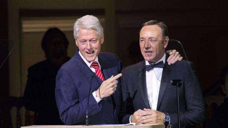 Former U.S. President Bill Clinton speaks to actor Kevin Spacey during the Rainforest Fund's 25th anniversary benefit concert in New York