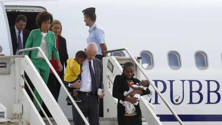 Mariam Yahya Ibrahim of Sudan carries one of her children as she arrives with Pistelli, Italy's vice minister for foreign affairs, holding her other child, and wife Agnese after landing at Ciampino airport in Rome