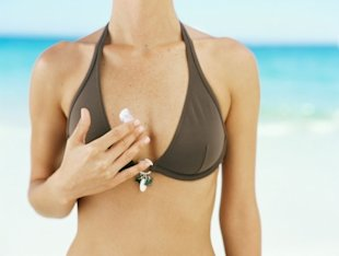 Woman applying sunscreen wearing bikini