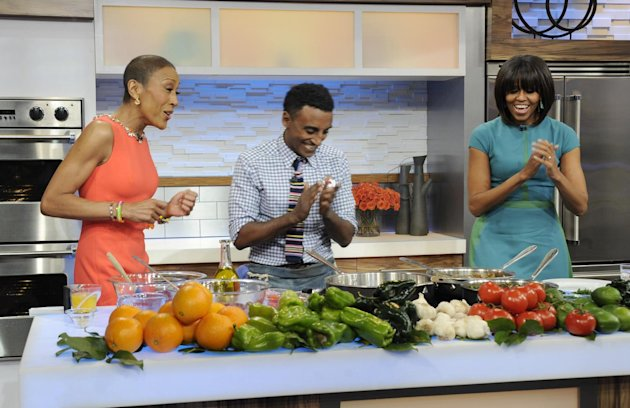 "This Feb. 22, 2013 photo released by ABC shows host Robin Roberts, left, chef Marcus Samuelson,, center, and first lady Michelle Obama during a taped segment on ""Good Morning America,"" in New York. Obama and Samuelson demonstrated some of her easy, healthy dishes and discussed nutritious recipes for busy families during her appearance airing Tuesday, Feb. 26. (AP Photo/ABC, Ida Mae Astute)"