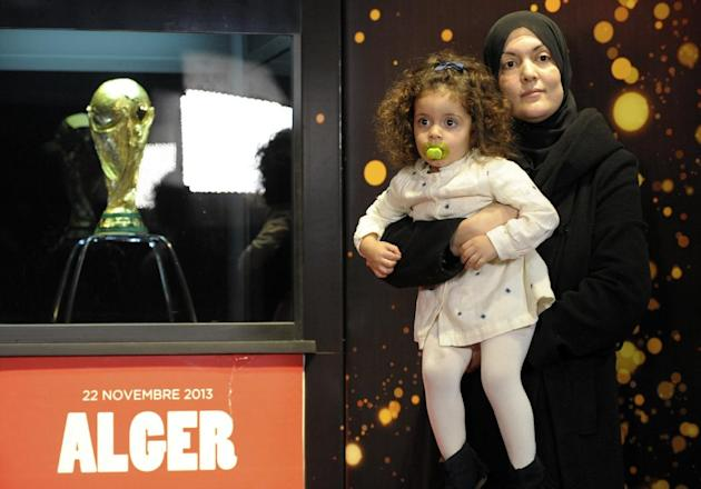 A woman holding her daughter poses for a sponsor photographer next to the FIFA World Cup Trophy, Friday, Nov. 22, 2013 in Algiers.  The trophy arrived Thursday for a two-day exhibition which will open