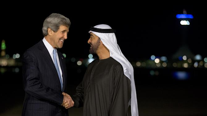 In this March 4, 2013, photo, U.S. Secretary of State John Kerry, left, and Crown Prince Mohamed bin Zayed shake hands for a photograph before their dinner meeting at the Emirates Palace hotel in Abu Dhabi, United Arab Emirates. With the smile of a seasoned politician, a flair for languages and a vast repertoire of personal anecdotes, Kerry schmoozed and cajoled his way through Europe and the Middle East on his first trip abroad as America's top envoy over the past 10 days. (AP Photo/Jacquelyn Martin, Pool)