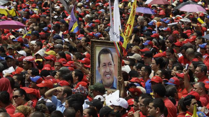 Holding a photo of Venezuela's late President Hugo Chavez, supporters of acting President Nicolas Maduro gather outside the national electoral council as he registers his candidacy to replace Chavez as president at the national electoral council in Caracas, Venezuela, Monday, March 11, 2013. Elections were announced to take place on April 14, after the death of Chavez on March 5.  (AP Photo/Fernando Llano)