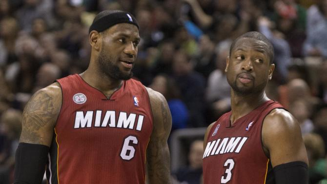 Miami Heat's LeBron James confers with Dwayne Wade during second half NBA basketball action against Toronto Raptors in Toronto on Sunday, March 17, 2013.  (AP Photo/The Canadian Press, Chris Young)