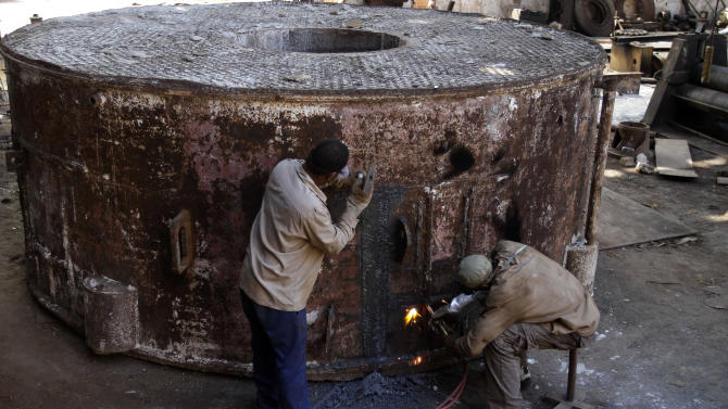 """In this Sept. 8, 2012 photo, Juan Penalver 52, right, and Jorge Luis Piss, 39, repair a boiler where sugar cane syrup is cooked at the sugar processing plant """"Brasil"""" in Jaronu, Cuba.  The Brasil sugar plant, launched in 1921, is getting a makeover and is expected to be ready in time for the upcoming annual harvest and start milling cane by February. (AP Photo/Franklin Reyes)"""