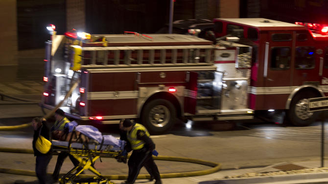 Emergency personnel wheel an injured victim from the scene of a gas explosion and massive fire Tuesday night, Feb. 19, 2013 at the Country Club Plaza in Kansas City, Mo. A car crashed into a gas main in the upscale Kansas City shopping district, sparking a massive blaze that engulfed an entire block and caused multiple injuries, police said. (AP Photo/The Kansas City Star, Tammy Ljungblad) KANSAS CITY OUT