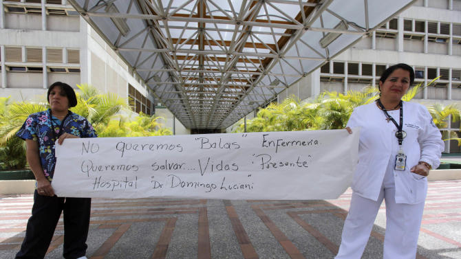 """In this Aug. 26, 2011 photo, nurses holds a poster that reads in Spanish, """"We don't want bullets, we want to save lives - Dr. Domingo Luciani Hospital,"""" as they demonstrate outside the hospital in Caracas, Venezuela. Bullets tore up the emergency ward of the Domingo Luciani Hospital in Caracas on Aug. 20, 2011. Employees said relatives and friends of a young man who died of gunshot wounds were enraged when they learned he had died and opened fire. Everyone escaped uninjured, and National Guard troops arrested the group that opened fire. (AP Photo/Fernando Llano)"""