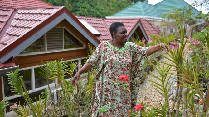 """In this March 14, 2013 photo, Jasmine Pottinger, a 73-year-old retired nurse, tends to her terraced backyard garden at her home in Mandeville, central Jamaica. Now retired in her Jamaican parish of birth, she worked four decades in London, a city where she never felt entirely accepted. For years, Jamaica has assisted nationals living abroad to undertake a sort of reverse migration back to the island, but the numbers of Jamaica's so-called """"returning residents"""", who moved to cities like London, New York or Toronto as young adults and dreamt that one day they would return to their sunny island, is steadily dwindling. (AP Photo/David McFadden)"""