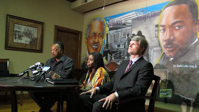 The Rev. Jesse Jackson, left, Teresa Carter, center, and Carter's attorney Ben Irwin speak at a news conference at Monumental Baptist Church Wednesday, Aug. 22, 2012 in Memphis, Tenn. about the death of Carter's son, Chavis Carter while he was in police custody in Jonesboro Ark. Jackson is calling on the Justice Department to investigate the death of a 21-year-old man who was shot in the head while handcuffed in the back of a patrol car. The three are sitting in front of a mural depicting the moments immediately after the shooting of Martin Luther King Jr. on April 4, 1968 at at the Lorraine Motel in Memphis.(AP Photo/Adrian Sainz)