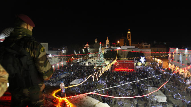 A Palestinian security officer stands guard as Christian worshippers and tourists celebrate at the Manger Square in front of the Church of the Nativity, in the West Bank town of Bethlehem, Monday, Dec. 24, 2012. Thousands of Christian worshippers and tourists arrived in Bethlehem on Monday to mark Christmas at the site where many believe Jesus Christ was born. (AP Photo/Adel Hana)