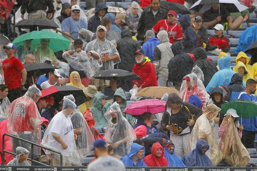 Fans take cover as a rain delay is called in the sixth inning of a baseball game between the Los Angeles Dodgers and the Atlanta Braves, Sunday, May 19, 2013, in Atlanta