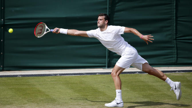Grigor Dimitrov of Bulgaria stretches to return to Grega Zemlja of Slovenia during their Men's second round singles match at the All England Lawn Tennis Championships in Wimbledon, London, Thursday, June 27, 2013. (AP Photo/Sang Tan)