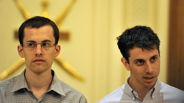 """Freed Americans Shane Bauer, left, and Josh Fattal speak to reporters before leaving for the United States at the airport in Muscat, Oman, Saturday, Sept. 24, 2011. Two Americans freed from an Iranian prison told reporters Saturday they were """"eager to go home"""" just before boarding their flight to the U.S. from Oman, the Gulf state that helped mediate their release after more than two years in custody on accusations of spying. Josh Fattal and Shane Bauer were scheduled to arrive home on Sunday, according to Samantha Topping, a spokeswoman for their families. The two were released from Tehran's Evin prison under a $1 million bail deal and arrived in Oman on Wednesday in the first leg of their journey home. There they were reunited with joyful relatives. (AP Photo/Sultan al-Hasani)"""