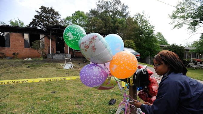 Neighbor Ameshia Stegall ties balloons to the mailbox after a fatal house fire killed five, including four children, in Newnan, Ga., Saturday, April 27, 2013.  The fire killed Alonna T. McCrary, 27, as well as her 5-year-old daughter Eriel McCrary and 2-year-old daughter Nikia White, according to Glenn Allen, the Georgia state Insurance commissioner's spokesman. Two other children, Messiah White, 3, and McKenzie Florence, 2, also died. Allen said the two were sleeping over at the home. A fifth child, 11-year-old Nautica McCrary, escaped the burning home and was taken to a hospital to be treated for smoke inhalation. (AP Photo/David Tulis)
