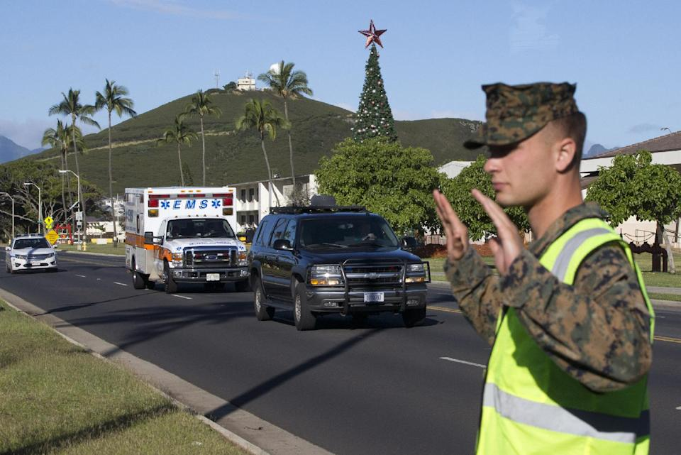 The motorcade carrying President Barack Obama is seen as it  passes a large tree decorated for Christmas and a Marine, Friday, Dec. 26, 2014, at...