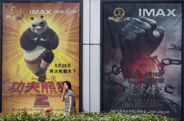 "In this photo taken on June 15, 2011, a woman walks past movie posters of Hollywood movies ""Kung Fu Panda 2,"" left, and China's propaganda film ""Beginning of the Great Revival"" on display side by side outside a cinema in Beijing. DreamWorks Animation and Chinese partners announced plans Tuesday, Aug. 7, 2012 to co-produce the next ""Kung Fu Panda"" movie and develop an entertainment district in Shanghai, expanding Hollywood's fast-growing ties to China. (AP Photo/Andy Wong)"
