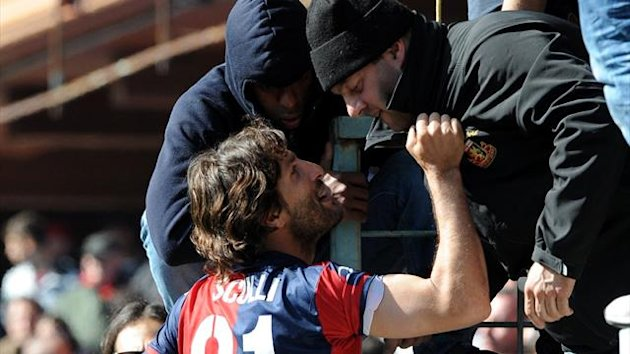 Genoa's Giuseppe Sculli climbs atop barriers to talk with supporters after the Serie A soccer match between Genoa and Siena was suspended at Genoa's Luigi Ferraris stadium, Italy, Sunday, April 22, 2012. Siena beat Genoa 4-1 in a match that was suspended