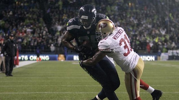 Seattle Seahawks' Anthony McCoy (L) scores a touchdown on a pass from quarterback Russell Wilson in the second quarter of their NFL football game against the San Francisco 49ers in Seattle, Washington, December 23, 2012.
