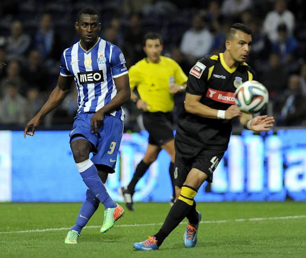 FC Porto's Jackson Martinez, left, from Colombia shoots to score his team's fourth goal past Arouca's Diego Queiroz, from Brazil, in a Portuguese League soccer match at the Dragao stadium,