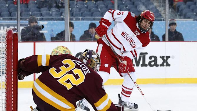 Minnesota goalie Adam Wilcox, left, watches the shot by Wisconsin forward Michael Mersch (25) sail wide of the net during the first period of a college hockey game at Chicago's Soldier Field, Sunday, Feb. 17, 2013. (AP Photo/Charles Rex Arbogast)
