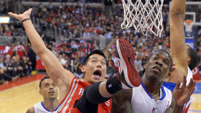 Houston Rockets guard Jeremy Lin, center, falls after putting up a shot as Los Angeles Clippers guard Eric Bledsoe, right, defends and forward Matt Barnes watches during the first half of their NBA basketball game, Wednesday, Feb. 13, 2013, in Los Angeles. (AP Photo/Mark J. Terrill)