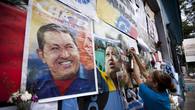 A supporter of Venezuela's late President Hugo Chavez places a message on the wall of the Venezuelan Embassy in Buenos Aires, Argentina on Saturday, March 9, 2013. Chavez died on March 5, 2013 after a nearly two-year bout with cancer. (AP Photo/Victor R. Caivano)