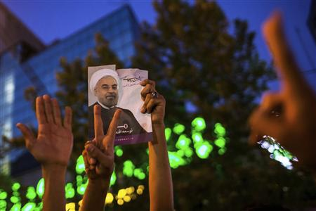 Supporters of moderate cleric Hassan Rohani hold a picture of him as they celebrate his victory in Iran's presidential election on a pedestrian bridge in Tehran June 15, 2013. REUTERS/Fars News/Sina Shiri