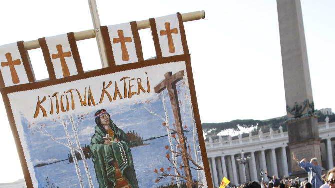 Native Indians from Quebec, Canada, hold an image of Kateri Tekakwitha, the first American Indian to achieve sainthood, as they wait for the start of a canonization ceremony celebrated by Pope Benedict XVI, in St. Peter's Square, at the Vatican, Sunday, Oct. 21, 2012. The pontiff will canonize seven people, Kateri Tekakwitha, Maria del Carmen, Pedro Calungsod, Jacques Berthieu, Giovanni Battista Piamarta, Mother Marianne Cope, and Anna Shaeffer. (AP Photo/Andrew Medichini)
