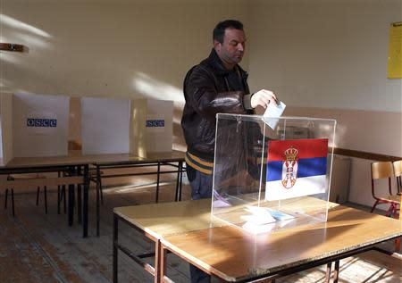 A man casts his vote at a polling station during Serbian elections in Kosovo's town of Mitrovica